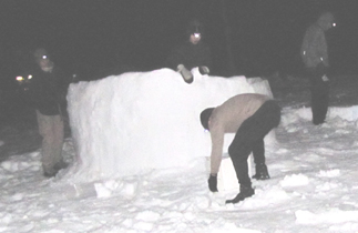 2010 building igloo at night: photo taken at night as campers build a round wall of snow five feet high, not quite finishing an igloo. Photo by Alan Ahlstrand