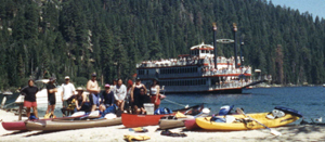 em bay kayaks: In the foreground, club kayaks and kayakers on beach at Emerald Bay. In the background, paddlewheel tourboat on the water.