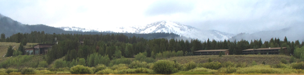 Jackson lake lodge as seen from inner park road: snow capped mountains and clouds in background, forested low hill with two large buildings