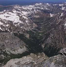 NPS photo N. Fork of Cascade Canyon as seen from the summit of the Grand Teton July 2010: tree covered canyon with snow capped mountains above