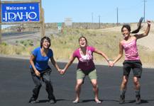 Phung, Kelly and Christina at Idaho border: three smiling grinning ladies with Idaho sign in background