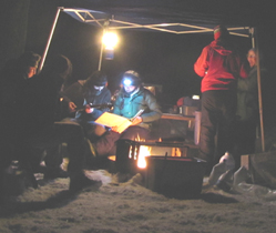 campfire songs winter 2010 210 pixels: nighttime shot of at least a foot of snow on the ground, a blazing campfire, guitarist seated at picnic table with other campers looking at songbooks and singing
