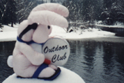club bunny in snow: a stuffed rabbit sitting on a snowbank, banging a drum that says Outdoor Club