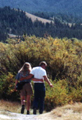 couple on tetons trail: couple walking together on a trail with hills in background