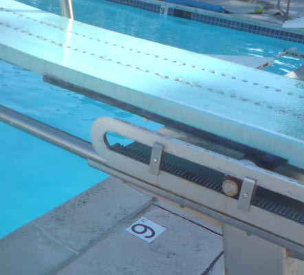 divingboard with only 9 feet water depth under: showing part of a 1 meter diving board with a tile in the pool deck below it saying 9 feet, the water depth under the board