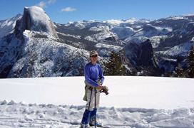 glacierpoint-winter NPS photo: cross-country skier and snow in foreground, peaks, including Half Dome, in background