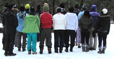 group photo 2012 snow camp: people standing in rows in the snow with their backs turned to the camera