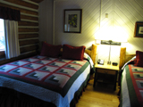 jenny lake lodge cabin interior: jenny lake lodge cabin interior with quilts on the two beds