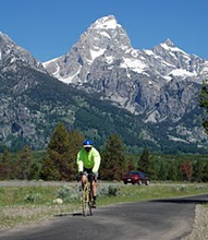nps photo bike path and peaks: cyclist approaching on paved bike path with peaks in background