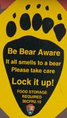 sign be bear aware in shape of footprint: