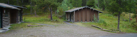 two colter bay cabins: two wood cabins and a large gravel parking area