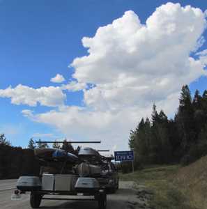 welcome to Idaho 2010: sign that says Welcome to Idaho, with mass of clouds in background, trailer of kayaks in foreground