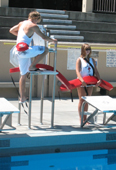 Alanna Klassen and Ethan Wilkie rotate guarding stations 2: one lifeguard climbing up stand ladder while one is on deck level