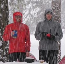 Eric and Alex breakfast 2011 winter trip: snow covered picnic table with stove, two guys holding mugs
