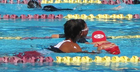 Howard Ho Wai Mok assists swimmer at the Silicon Valley Kids Triathlon: lifeguard helps an athlete finish the swim portion of a triathlon