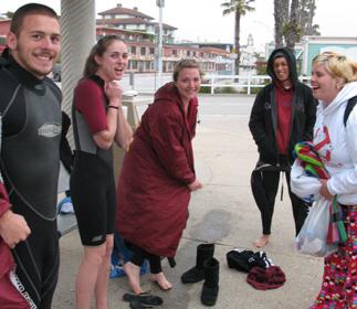 "I'm going to fit my whole body in that hole: five waterfront lifeguard candidates laughing over fitting into a wetsuit, one saying ""I'm going to fit my whole body in that hole"" (at the neck in the top of the wetsuit)"