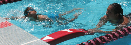 Joyce Kuo with swimmer at 2010 Kids tri: lifeguard with rescue tube swims next to small child photoshop smudge tool used to protect child's identity