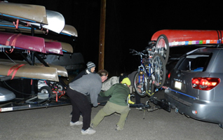 Mila and crew move kayak trailer: people pulling a kayak trailer into posistion to hook it up to a S U V