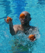 Mitchell Conley juggles while treading water: man juggles three balls while in a swimming pool