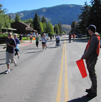 Old Bill's Fun Run volunteer Mark Nevill: man with orange flag standing in roadway as runners, walkers and one person with a stroller go by