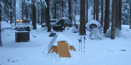 Outdoor club campsite last morning 2011 winter trip: snow covered cars, tents, picnic tables