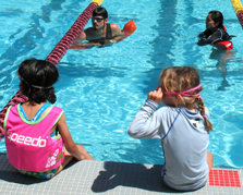 Paul Barron and Bernadette Milan at Kid's tri: two adult lifeguards in the pool with two young girls at pool edge just before a triathlon swim photo by Alan Ahlstrand, Red Cross Lifeguard Instructor and Volunteer of Record for De Anza College