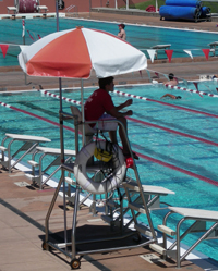 Avery Aquatic Center lifeguard with feet on rescue tube: