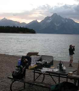 dinner at Colter Bay lakeside picnic area: sunset along the Teton range at a picnic area by a lake. Man standing with binoculars, picnic table full of dinner and gear at Colter Bay lakeside picnic area