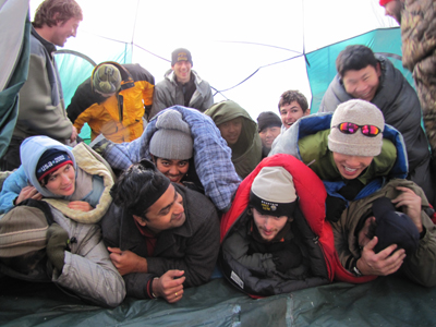 forming the group in the tent photo 2010: campers in sleeping bags setting themselves into a pile for a photo of 12 people in an eight person tent, laughing at jokes about who is on top
