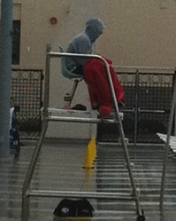 fremont high school guard in stand: closer view of lifeguard on duty in stand with parka wrapped around him and his feet on his rescue tube