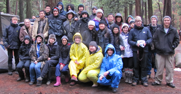 group photo Yosemite winter trip 2014: 30 people in rain gear sitting or standing on a picnic table in a Yosemite campsite