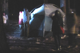 group pitching tent snow camp 2011: group of people pitching tent after dark