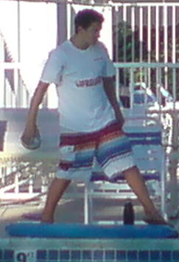 lifeguard tossing football: A lifeguard on duty at a pool tossing a football. His rescue tube is on the ground in front of him.