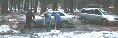 shoveling snow at campsite parking space: three people shoveling snow to clear a campsite parking space