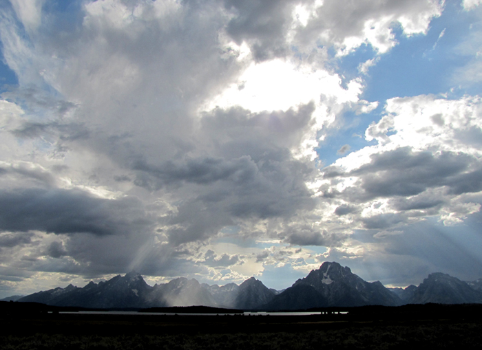sunlight streaming through clouds teton range Sept 2011: photo mostly of clouds with a mountain range in the distance and little light on a lake in the mid distance