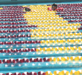 svkt swimmer needing assistance 2010: rows of pool lane lines with one adult lifeguard and one swimmer in need of a rescue tube to hold on to and kick photo by Alan Ahlstrand