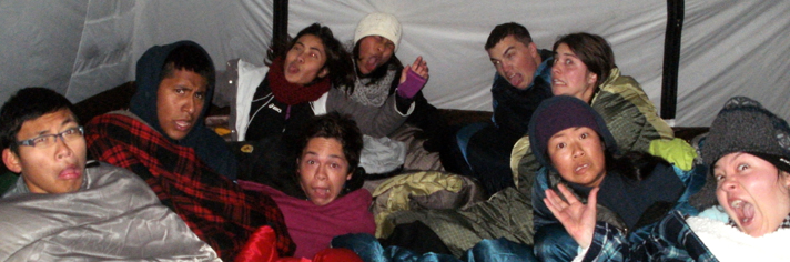 unhappy with too many people in tent 2013: a bunch of people sitting up in their sleeping bags in a tent making faces