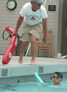 volunteertrilifeguardAlanAhlst.rand: lifeguard leaning towards swimmer supported by a noodle