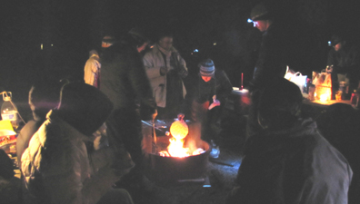 warming a tortilla at a campfire: People at picnic tables and around campfire. One is roasting a marshmallow, another is holding a tortilla over the flames.