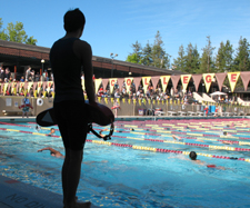 187 PIXELS GUARDING KID'S TRI: lifeguard silhouetted with pool and swimmers in brighter light photo by Alan Ahlstrand, Red Cross Lifeguard Instructor and Volunteer of Record for De Anza College