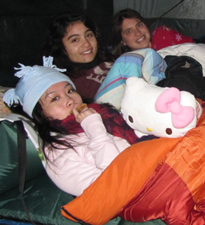 3 girls in tent 2011 winter: 3 girls in a tent in their sleeping bags, wearing knit hats