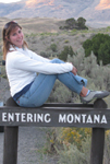 Alanna Klassen on Montana sign photo by mark Nevill: girl sitting on top of a wooden sign that says Entering montana