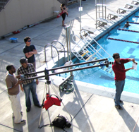 lifeguard to the stars Alanna Klausen: movie crew filming in foreground, lifeguard in background at De Anza College pool