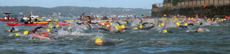 Alcatri start 2010: a mass of swimmers and kayakers on San Francisco bay with part of Alcatraz island in the background