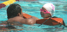 JulioBazanandswimmerkidstri 130 pixels: lifeguard assists smiling child at swim race