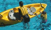 Mimi climbing into kayak: