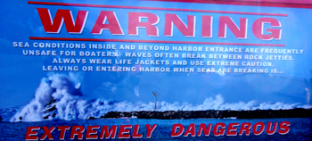 Morro Bay Harbor warning sign: Morro Bay Harbor warning sign with photo of a large boat caught in an even bigger wave at the entrance to the harbor.