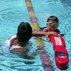 SVKTkickingwithrescuetube 234 pixels: child holds on to end of rescue tube with lifeguard also holding tube