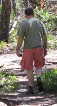 String Lake hiker with diet soda: a man off on a hike, in hiking boots, shorts and a t-shirt, carrying a half liter of diet soda and not much else