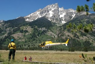 Teton interagency helicopter NPS photo: helicopter lifts off with Teton mountains in background
